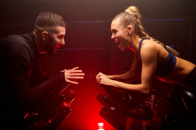 Homem e mulher disputam uma competição de bicicleta na academia de ginástica, andando de frente um para o outro, com agasalho de ginástica, gritando