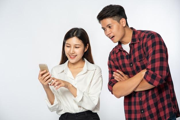 Homem e mulher divertem-se com selfies em seus smartphones