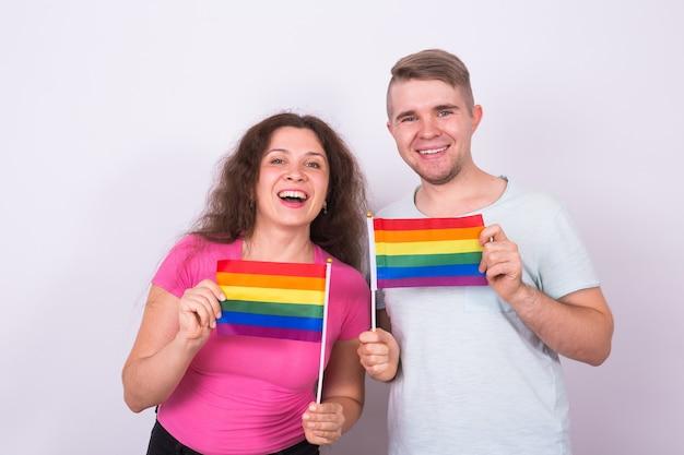 Homem e mulher divertidos em pé com bandeiras de arco-íris