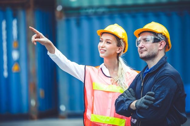 Homem e mulher do trabalhador logístico trabalhando em equipe com controle de rádio, carregando contêineres no porto de carga para caminhões para exportação e importação de mercadorias.
