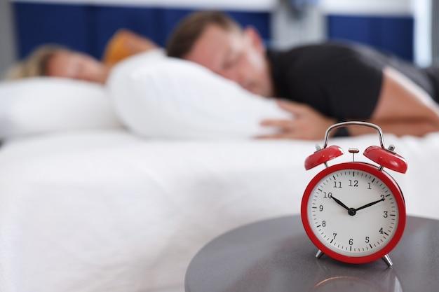 Homem e mulher dormem no quarto no despertador às dez da manhã, tarde da noite, sono no fim de semana