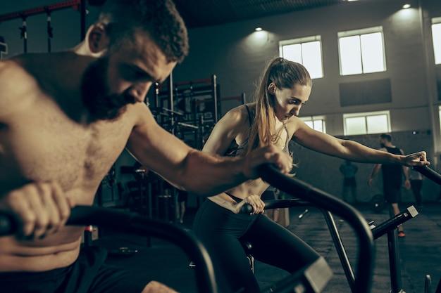 Homem e mulher durante exercícios no ginásio de fitness.