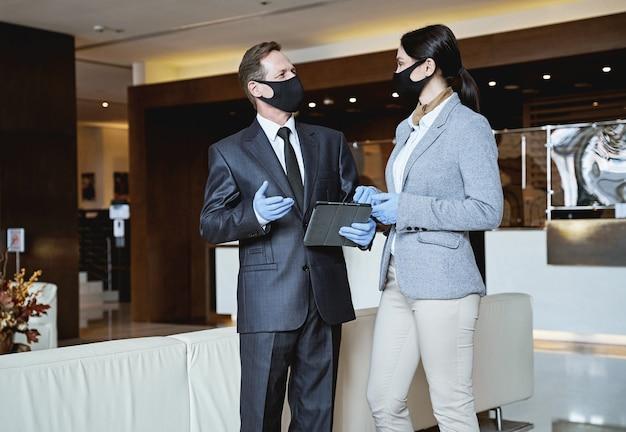 Homem e mulher elegantes com máscaras médicas e luvas de borracha olhando um para o outro enquanto se comunicam no saguão de um hotel