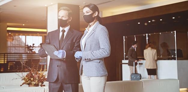 Homem e mulher elegantes com máscaras médicas em um corredor olhando para longe