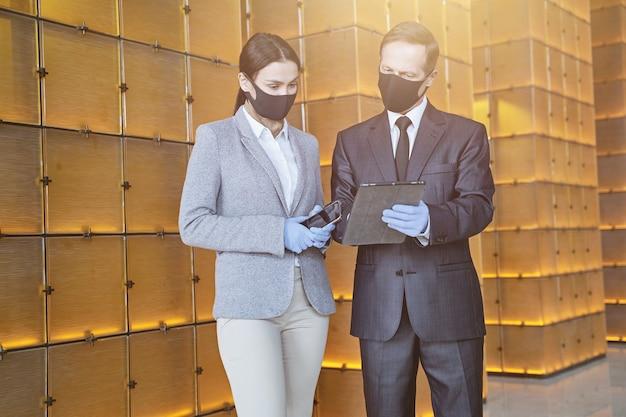 Homem e mulher elegantes em pé no corredor com máscaras médicas e luvas de borracha com aparelhos modernos nas mãos