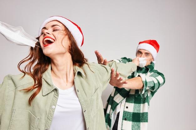 Homem e mulher em bonés de natal com máscara médica e diversão juntos