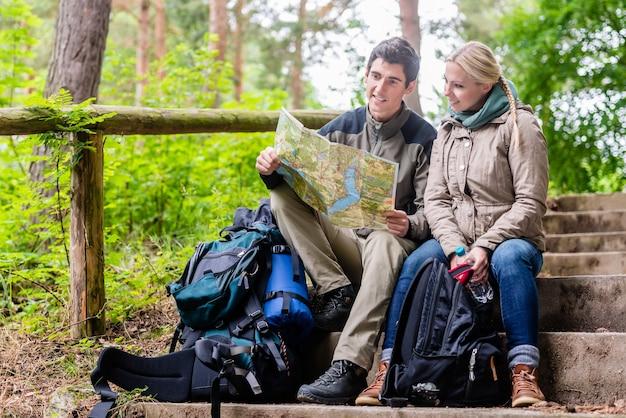 Homem e mulher em caminhada na floresta, planejando a próxima seção da rota no mapa