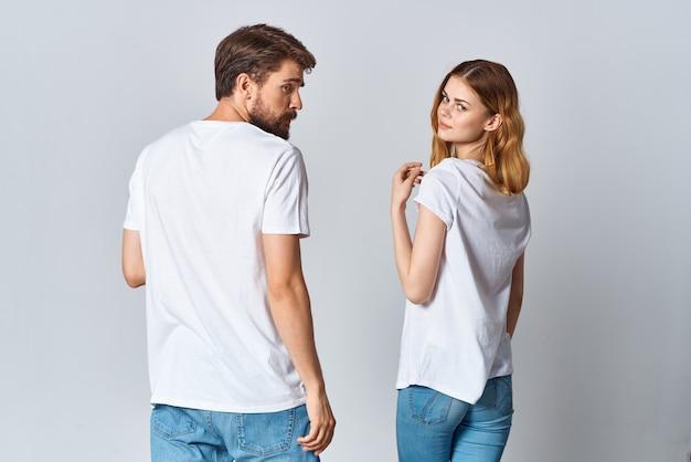 Homem e mulher em camiseta branca em pé com a maquete de fundo claro nas costas