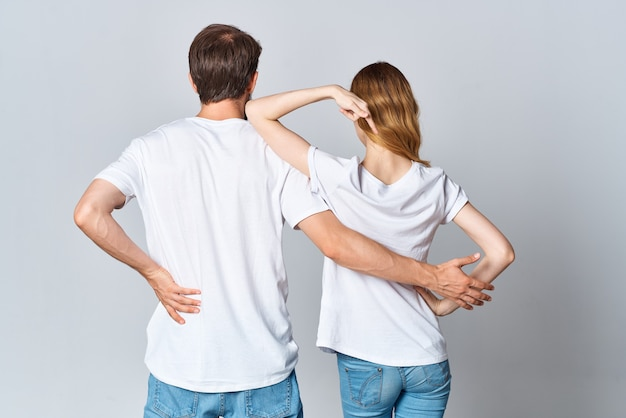 Homem e mulher em camiseta branca em pé com o estúdio de design de costas