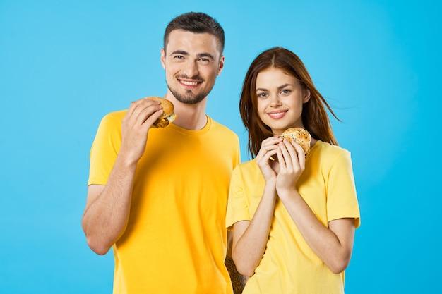Homem e mulher em camisetas amarelas com hambúrgueres nas mãos fast food