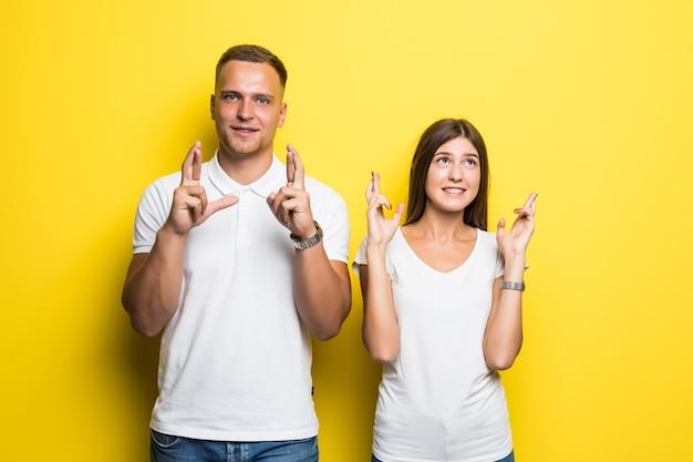 Homem e mulher em camisetas brancas segurando os dedos cruzados isolados em um fundo amarelo