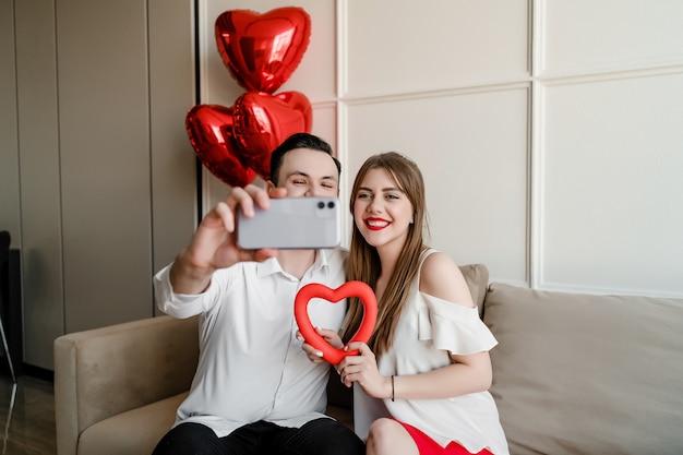 Homem e mulher em casa fazendo selfie com coração e balões no telefone