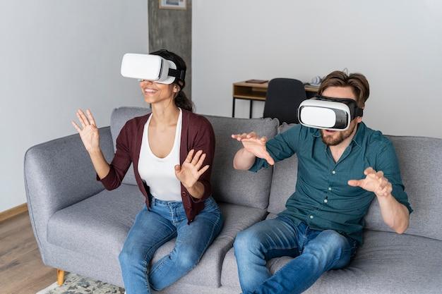 Homem e mulher em casa no sofá com fone de ouvido de realidade virtual