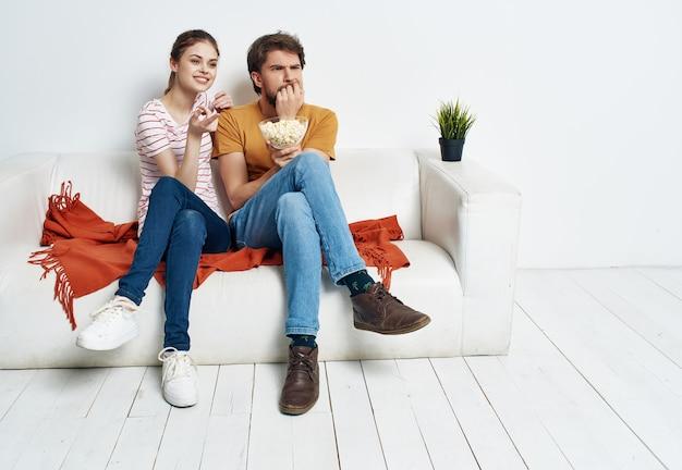Homem e mulher em casa no sofá com pipoca assistindo filmes relaxantes