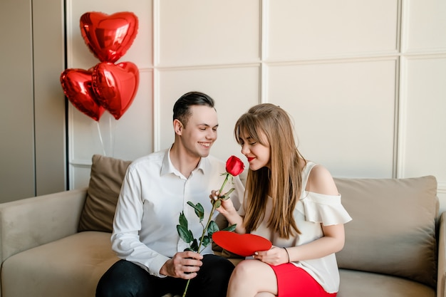 Homem e mulher em casa no sofá com rosa vermelha e coração em forma de cartão de dia dos namorados
