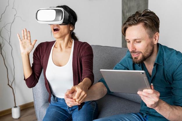 Homem e mulher em casa usando fone de ouvido de realidade virtual e tablet