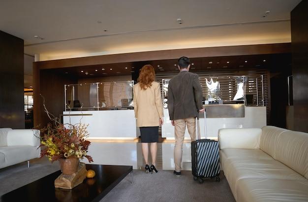 Homem e mulher em pé com suas bagagens em frente a uma recepção durante o check in