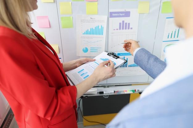 Homem e mulher em pé perto do quadro-negro, segurando documentos com gráficos closeup empresariais