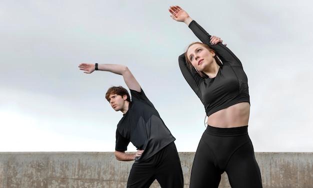 Homem e mulher em roupas esportivas se exercitando ao ar livre