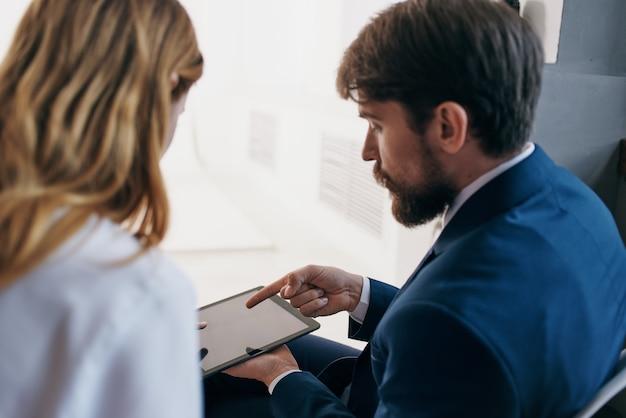 Homem e mulher em ternos de negócios se comunicam com o trabalho em equipe de funcionários do tablet. foto de alta qualidade