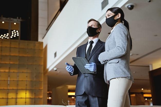 Homem e mulher em ternos e máscaras médicas em pé no saguão do hotel, olhando para a distância. comprimido nas mãos do homem