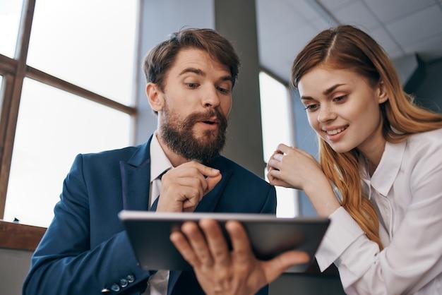 Homem e mulher em ternos executivos se comunicam com o escritório de tecnologia de tablets