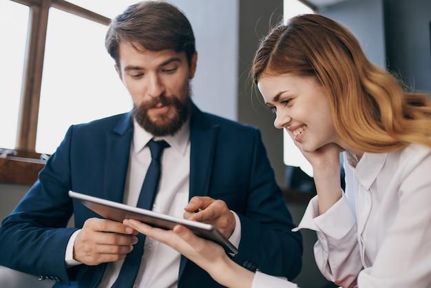 Homem e mulher em ternos executivos trabalham com um tablet. funcionários em equipe