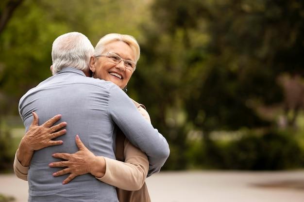 Homem e mulher em tiro médio se abraçando ao ar livre