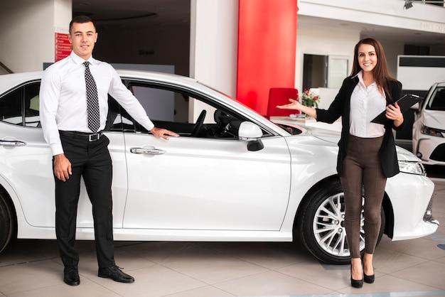 Homem e mulher em uma concessionária de carros
