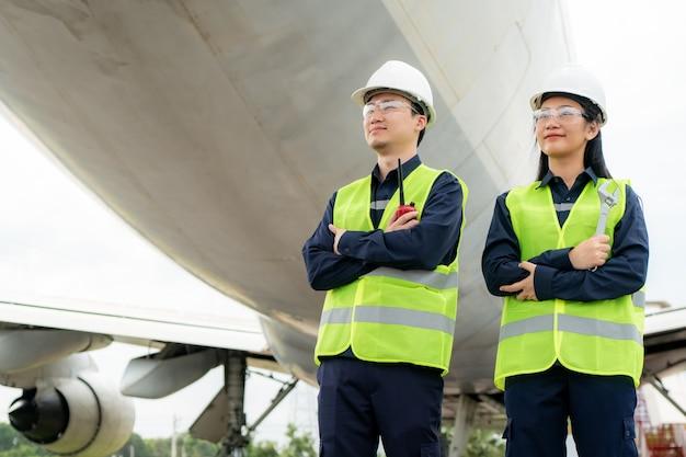 Homem e mulher engenheiro de manutenção, braço do avião cruzado e segurando a chave inglesa na frente do avião de reparos
