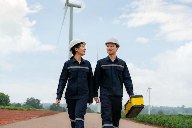 Homem e mulher engenheiros de inspeção preparando e verificação de progresso no parque eólico
