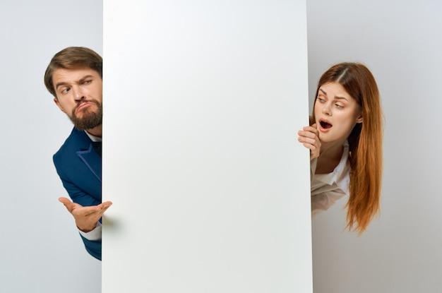 Homem e mulher engraçados com cartaz de maquete branco sinal de publicidade com fundo branco