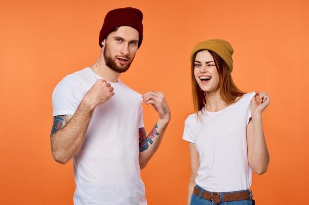 Homem e mulher engraçados em camisetas jovens roupas laranja fundo