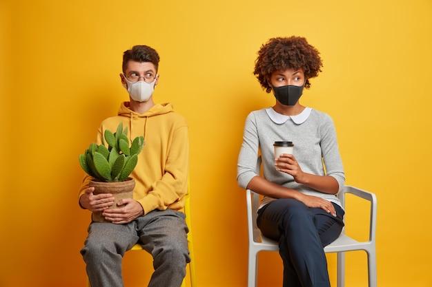 Homem e mulher entediados ficam em casa durante a quarentena, usam máscaras, bebem café e carregam cactos em vasos, sentam-se em cadeiras confortáveis e olham pensativamente para longe