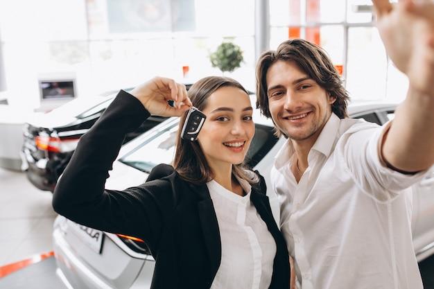Homem e mulher escolhendo um carro em uma sala de exposições