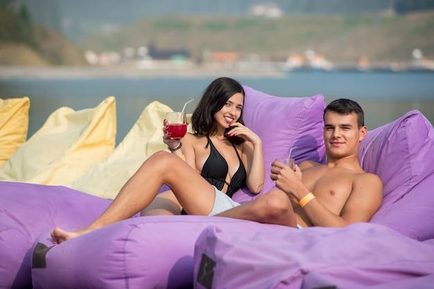 Homem e mulher estão curtindo a companhia um do outro com bebidas nas espreguiçadeiras macias do resort de luxo