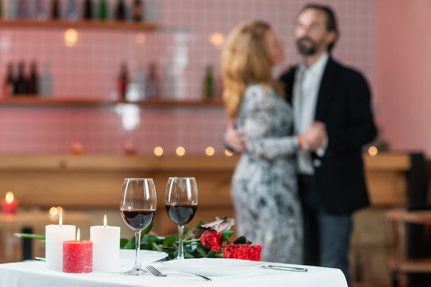 Homem e mulher estão dançando em um café, foco suave
