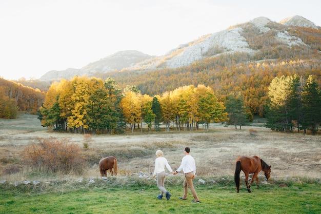 Homem e mulher estão de mãos dadas e caminham no gramado onde cavalos pastam no cenário de