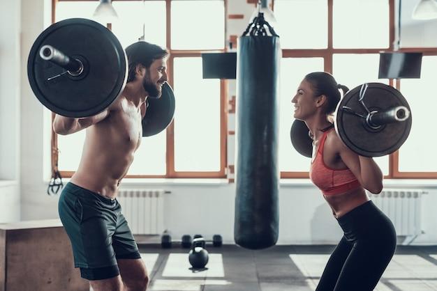 Homem e mulher estão levantando halteres no ginásio.
