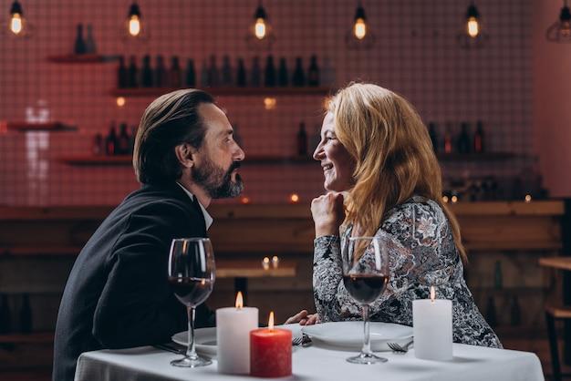 Homem e mulher estão olhando no amor um ao outro enquanto está sentado em uma mesa em um restaurante