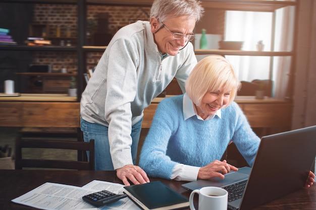 Homem e mulher estão olhando para a tela do laptop e rindo.