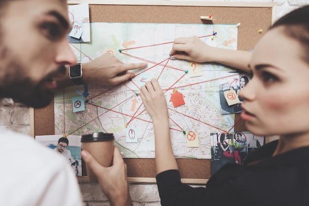Homem e mulher estão olhando para o mapa de pistas, bebendo café.