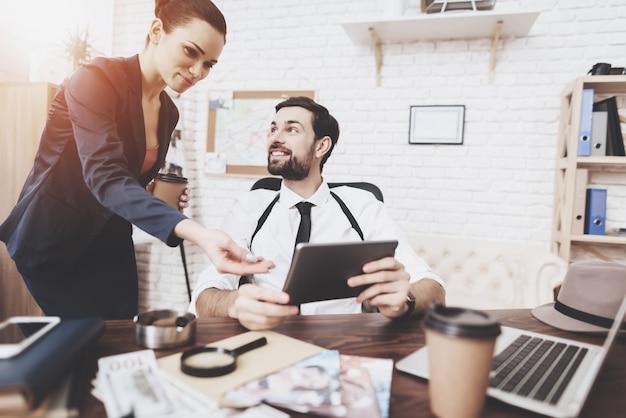 Homem e mulher estão olhando para tablet no escritório.