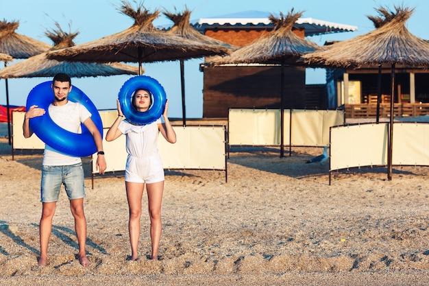 Homem e mulher estão posando na praia e segurando círculos infláveis. conceito de férias de verão no mar.