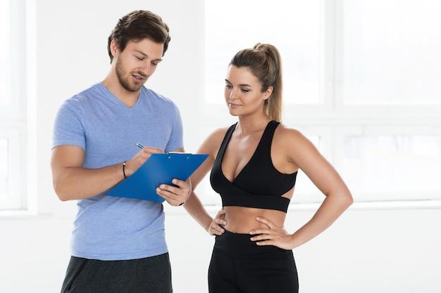 Homem e mulher estão prontos para se exercitar na academia. instrutor de fitness pessoal redigindo treinamento individual e plano de dieta para seu cliente