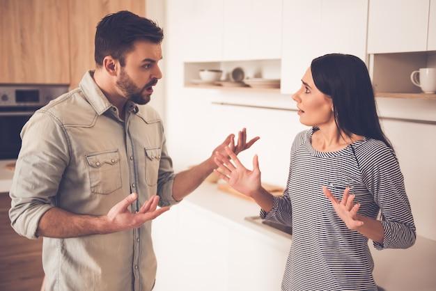 Homem e mulher estão repreendendo em pé na cozinha.