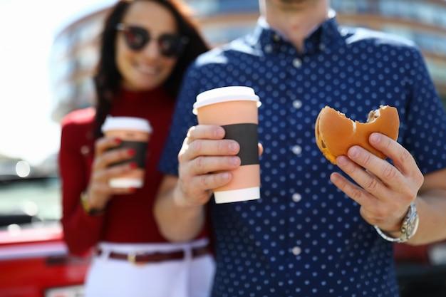 Homem e mulher estão segurando café e hambúrguer