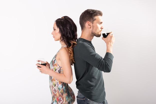 Homem e mulher estão segurando copos de cerveja escura em fundo branco. .