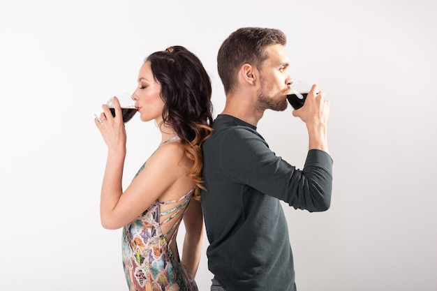 Homem e mulher estão segurando copos de cerveja escura na parede branca com espaço de cópia. conceito de oktoberfest.