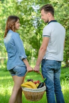 Homem e mulher estão segurando uma cesta de comida.